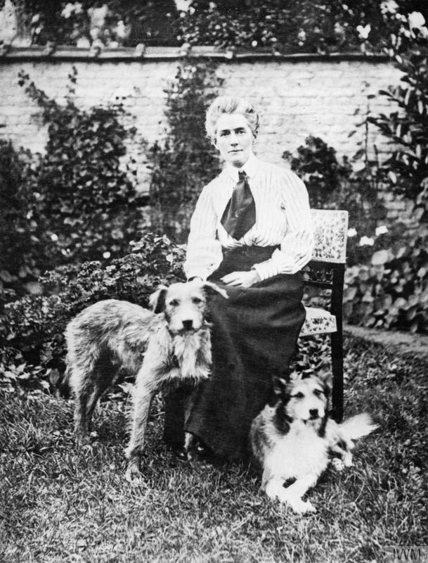 """Pre-War Life in Brussels - A portrait of nurse Edith Cavell as she sits in a garden her two dogs. The dog on the right, """"Jack"""" was rescued after her execution. -  © IWM Q 32930"""